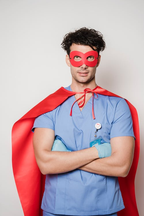 Serious male doctor in uniform and gloves wearing red superhero cape and mask looking at camera on white background in studio