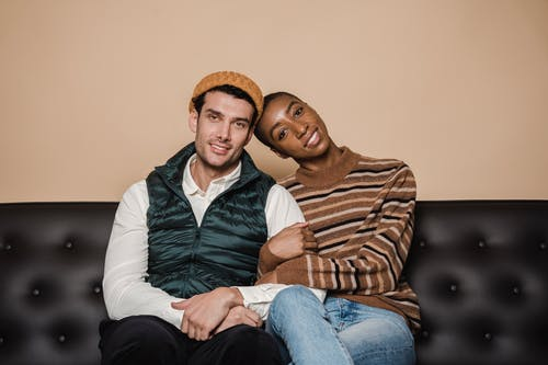Positive multiracial romantic couple in casual clothes embracing and looking at camera while sitting on sofa in living room at home
