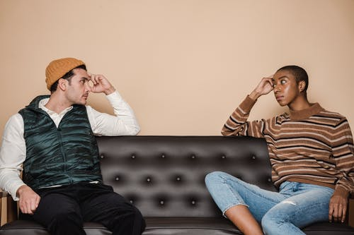 Diverse couple in casual clothes looking at each other with serious faces while sitting on sofa during quarrel in living room
