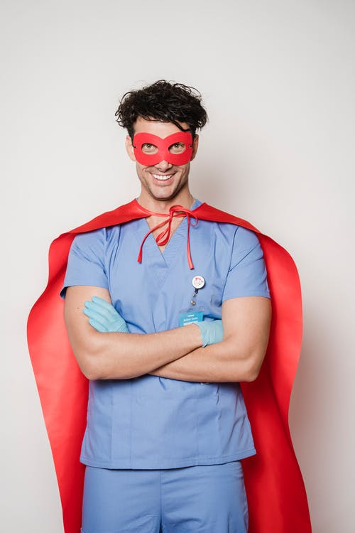 Positive male doctor wearing red cape and mask smiling and looking at camera while standing on white background with raised arms