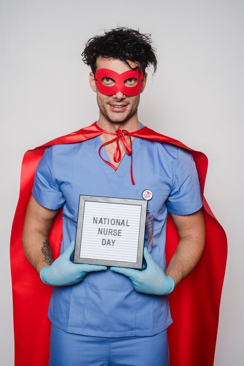 Doctor in superhero costume showing card with National nurse day inscription