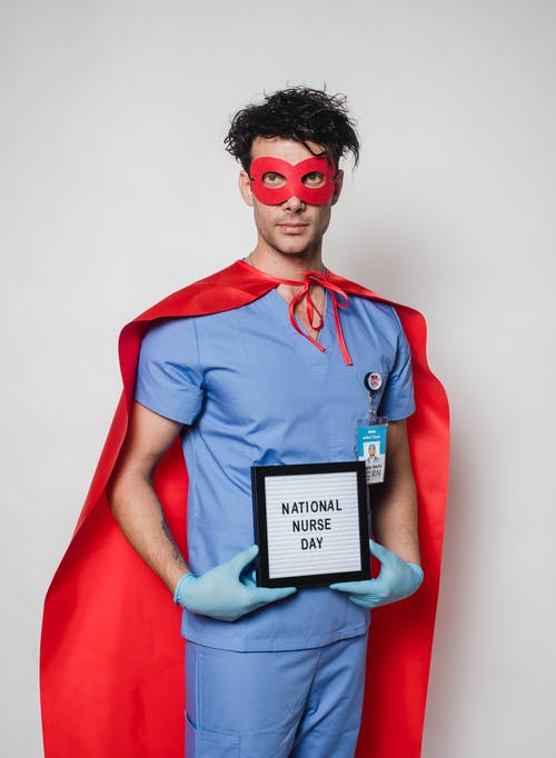 Serious doctor in superhero costume holding letterboard with National nurse day inscription