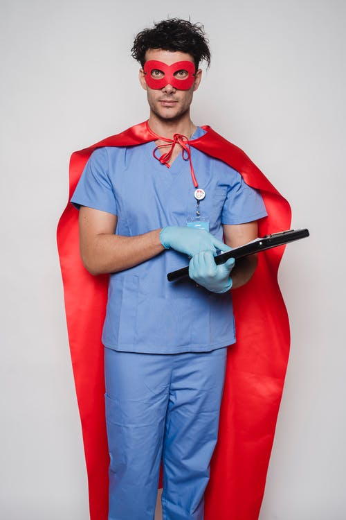 Calm doctor in uniform and superhero costume standing with clipboard and looking at camera against light background