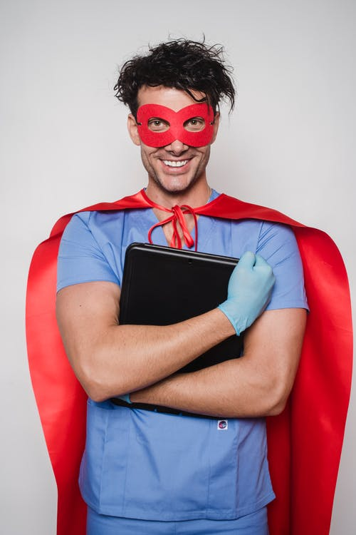 Cheerful man doctor in superhero costume with mask and cape standing with folder with documents and looking at camera against light wall