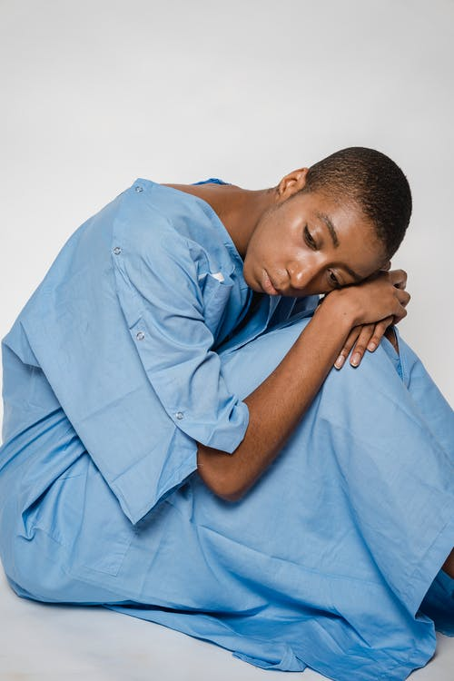Tired black woman patient sitting on floor and embracing knees in studio