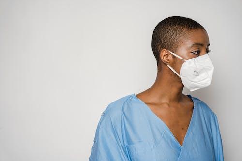 Black woman patient in mask looking away in light room