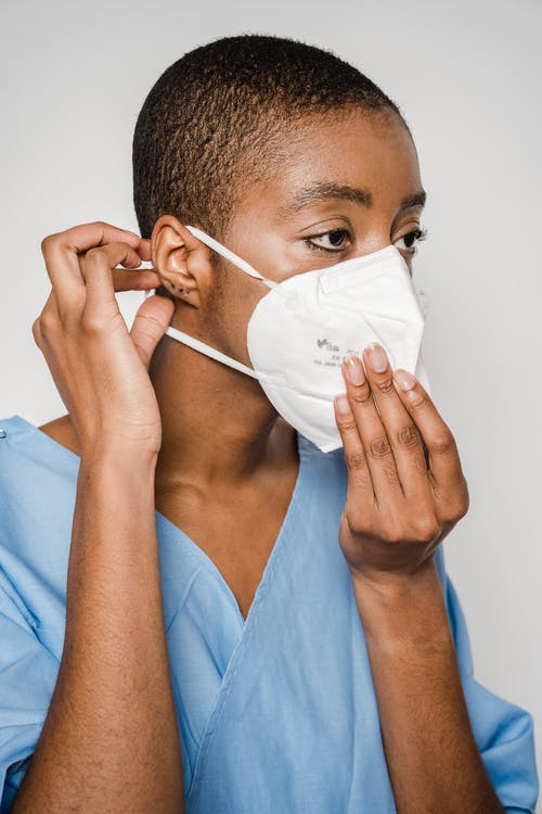 Young woman in medical uniform putting mask on
