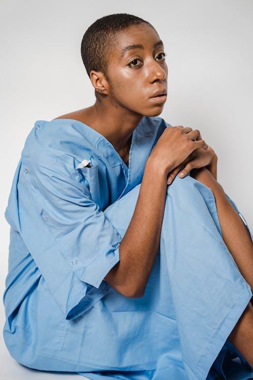 Pensive black woman in medical uniform of patient
