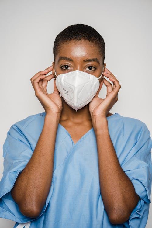 Black female doctor putting medical mask on face