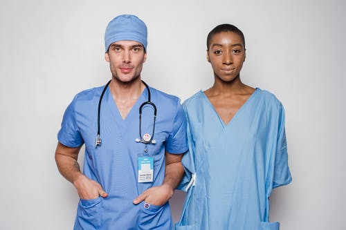 Positive male doctor in blue uniform with hands in pockets smiling and looking at camera while standing near nurse holding hands behind back in hospital