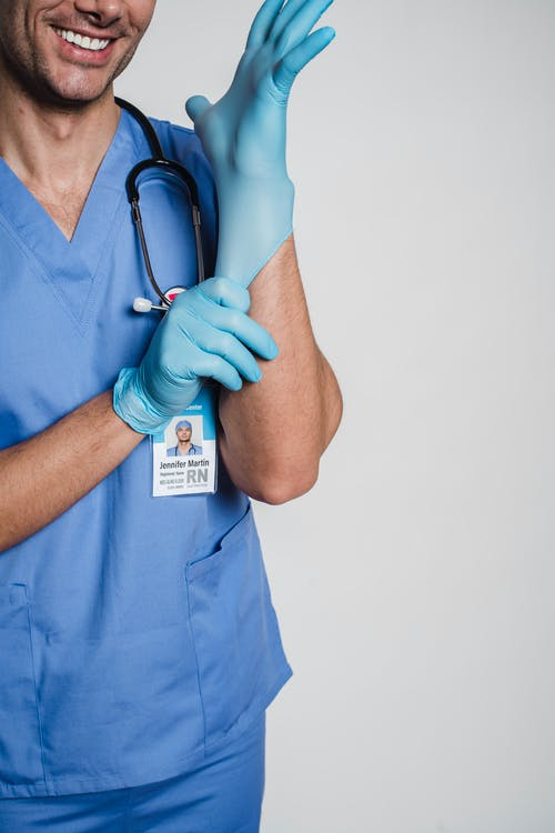 Anonymous doctor in uniform and gloves with stethoscope in studio