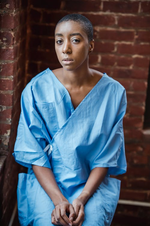 Thoughtful adult African American female patient wearing blue medical robe while sitting near brick building wall and looking at camera in light place