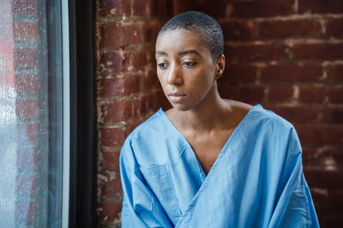 Pensive African American female patient with short dark hair in blue medical robe looking at window against brick wall in daylight