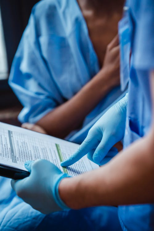 Crop unrecognizable doctor in uniform and sterile gloves showing clipboard with diagnosis to black anonymous patient