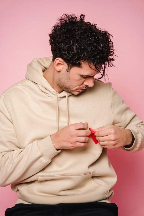 Man Pinning A Ribbon On His Hoodie