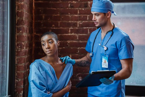 Man doctor in blue uniform and sterile gloves with stethoscope demonstrating diagnosis to thoughtful African American female patient in corridor of clinic in daytime