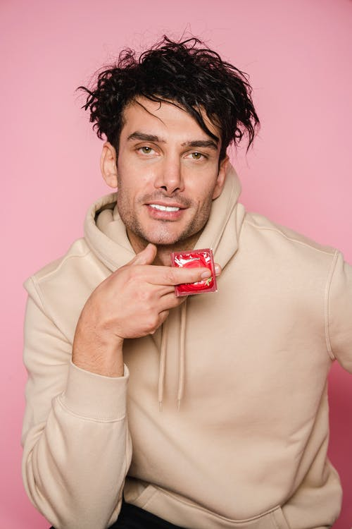 Charismatic man with curly dark hair in stylish clothes sitting with red condom in hand and looking at camera in studio against pink background