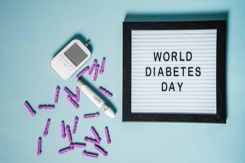 Top view of lancets for blood glucose meter placed near glucometer and letter board with World Diabetes Day inscription