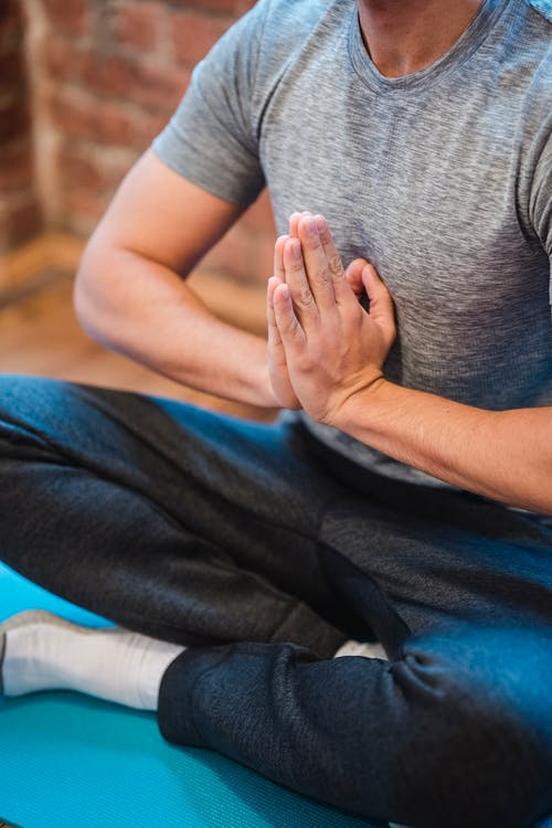 High angle of crop faceless male sitting with crossed legs in Sukhasana with praying hands on chest