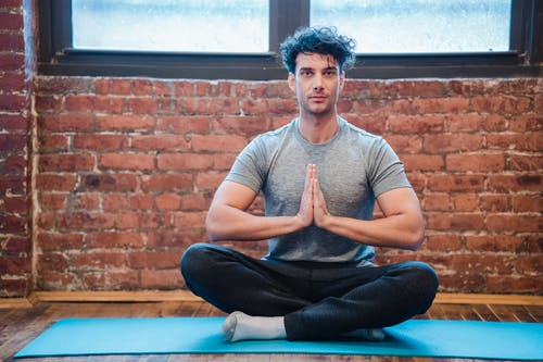 Full body of focused male sitting in Sukhasana with praying hands while practicing yoga on sports mat