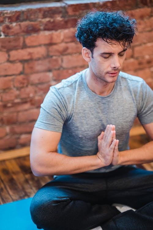 Focused male breathing during yoga practice in Easy Sit pose
