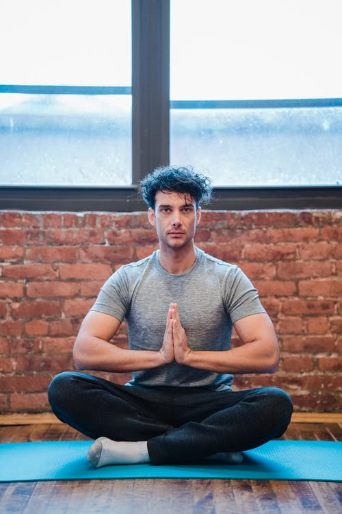 Meditating man sitting with crossed legs and namaste gesture