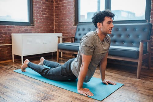 Side view full body of serious male doing backbend in Bhujangasana during yoga training on sports mat