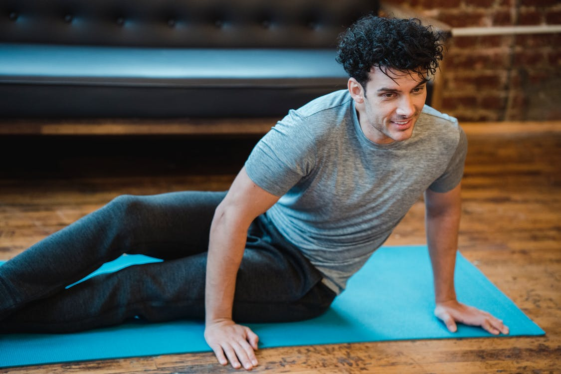 Smiling man doing twist exercise during workout