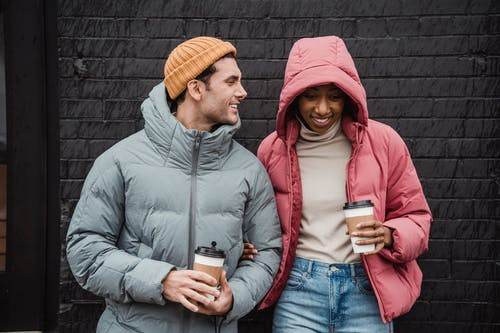 Positive multiethnic couple in outerwear standing close with cups of takeaway coffee on street