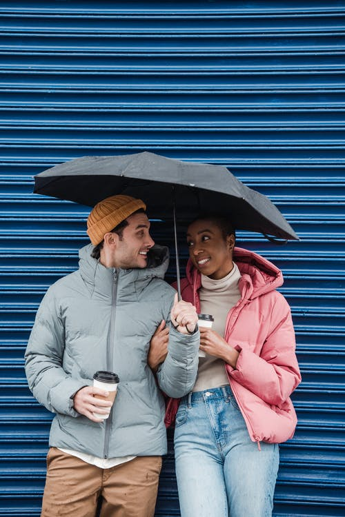 Happy multiethnic couple in outerwear standing with cups of takeaway coffee under umbrella and looking at each other with love