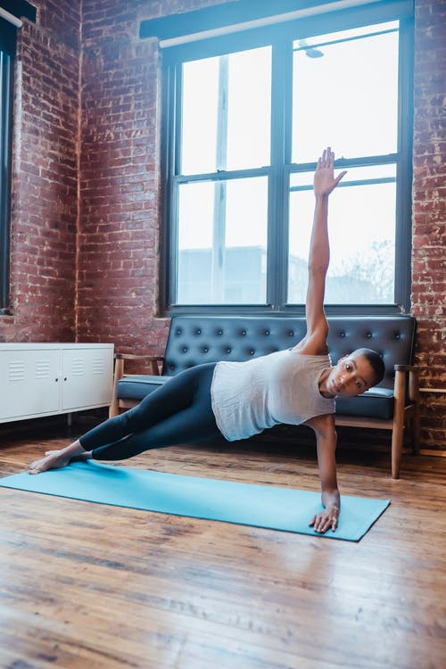 Full body of African American female doing Side Dolphin Plank with arm raised during yoga session