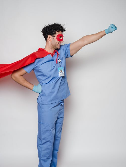 Positive male doctor in blue uniform with name tag under flying cape standing with hand on waist and fist forward against gray background