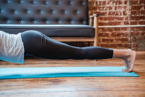 Side view of crop anonymous female in sportswear standing on tiptoes in Dolphin Plank posture during yoga practice