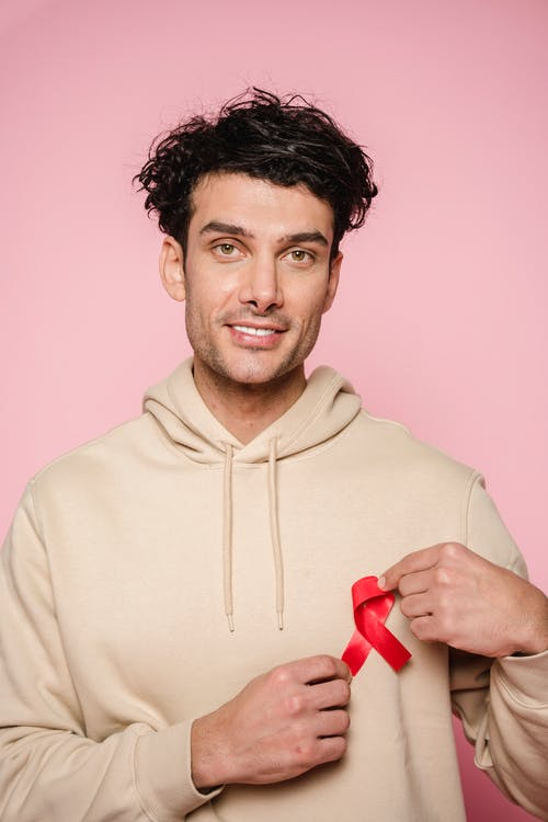 Man In A Hoodie Holding Red Ribbon