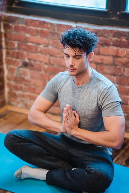 From above of male with eyes closed doing yoga in Padmasana at home with brick wall