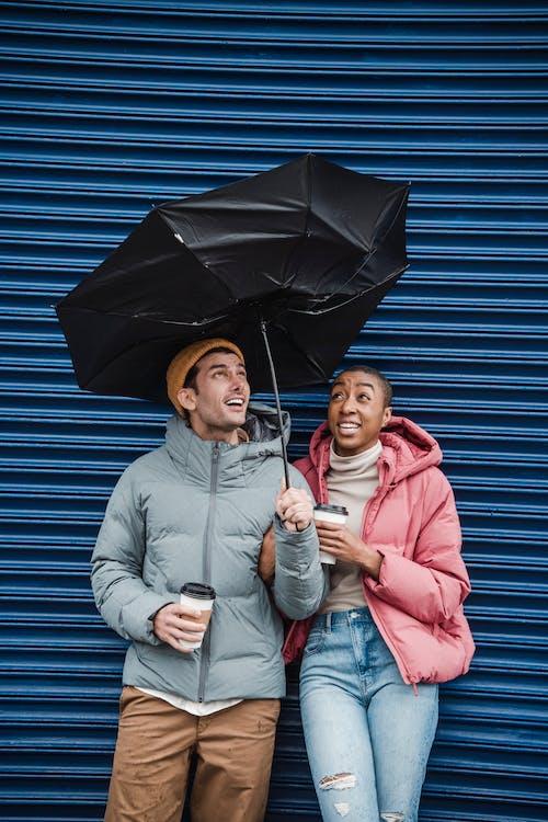 Woman in Pink Zip Up Jacket Holding Umbrella