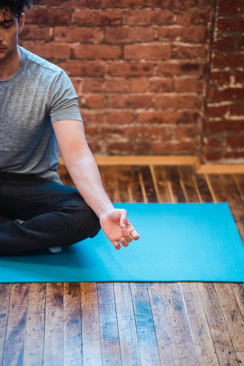 Man in Gray Crew Neck T-shirt and Black Pants Sitting on Blue Mat
