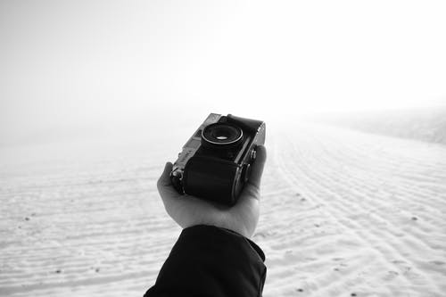 Black and white of crop anonymous male photographer with vintage photo camera in hand in snowy terrain