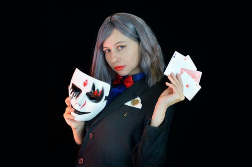 Side view of serious young female casino dealer in classy suit with bow tie holding face mask and cards in hands and looking at camera against black background