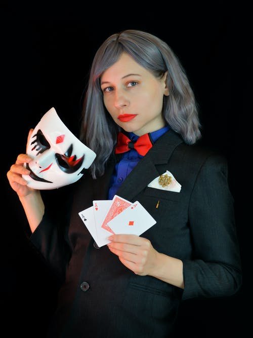 Stylish young female illusionist in elegant suit with red bow tie showing deck of cards and looking at camera while standing against black background with mask in hand