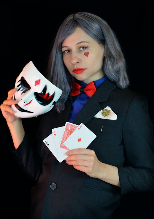 Stylish young lady with gray hair and with painted red heart symbol on face in costume with bow tie showing trick with playing cards and face mask in black studio