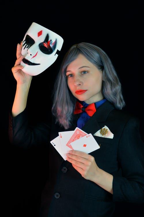 Calm young female magician showing performance with mask and playing cards