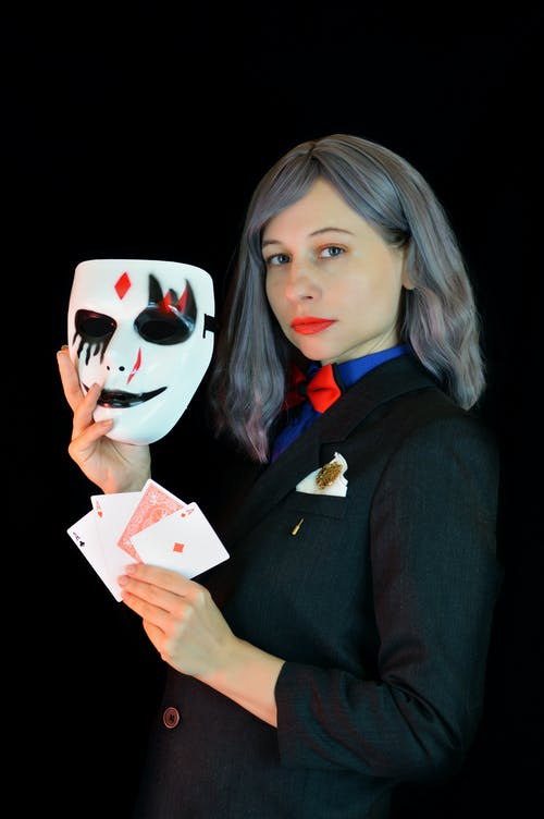 Side view of self esteem young female magician with gray hair and red lips in formal uit with red bow tie showing face mask and deck of cards
