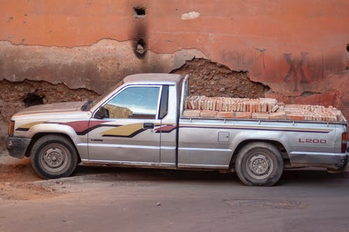 Old pickup car with heap of bricks in trunk parked on town street near shabby old building on sunny day