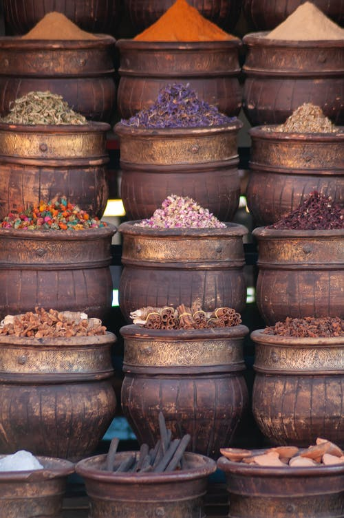 Traditional wooden pots with assorted colorful dried herbs and condiments in local bazaar in daytime