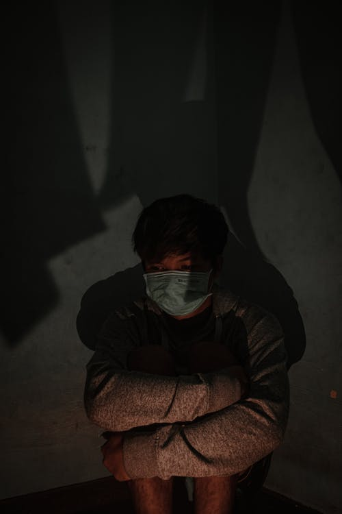 Depressed young ethnic man in protective mask sitting on floor and embracing knees