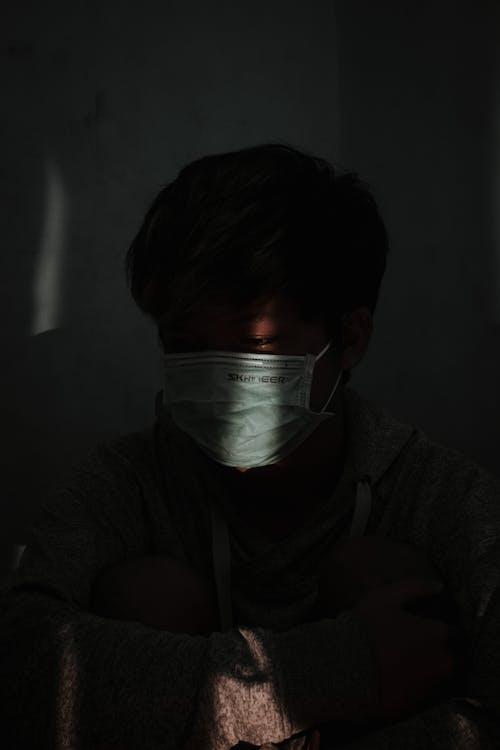 白いフェイスマスクを身に着けている灰色のパーカーの男