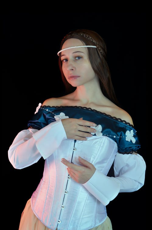 Attractive woman in medieval dress and pearl diadem in studio