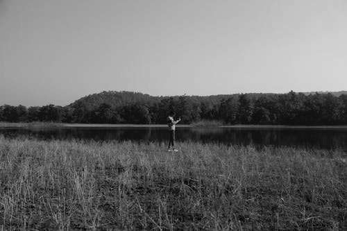 Grayscale Photo of Person Standing on Grass Field Near Lake