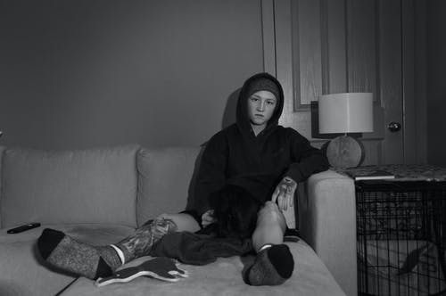 Grayscale Photo of Person Sitting on a Couch
